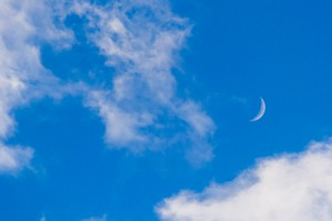 55615088 - bright blue sky with clouds and new moon